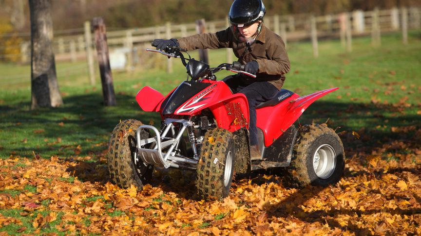 Honda TRX90X Sportrax 90 being ridden by child in a field.