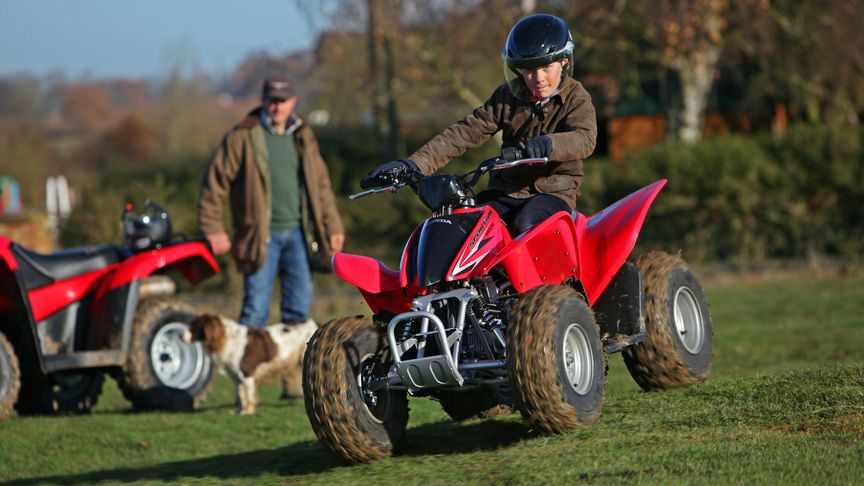 Honda trx90x sportrax being ridden by child in a field.