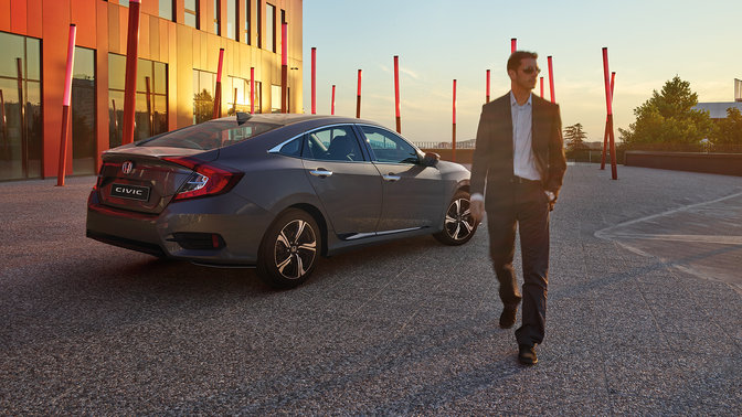 Elegant Rear Three Quarter Facing Honda Civic 4 Door With Driver.