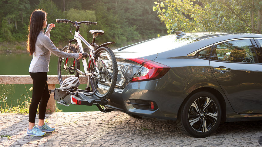 Side facing Honda Civic 4 door with Thule bicycle carrier.