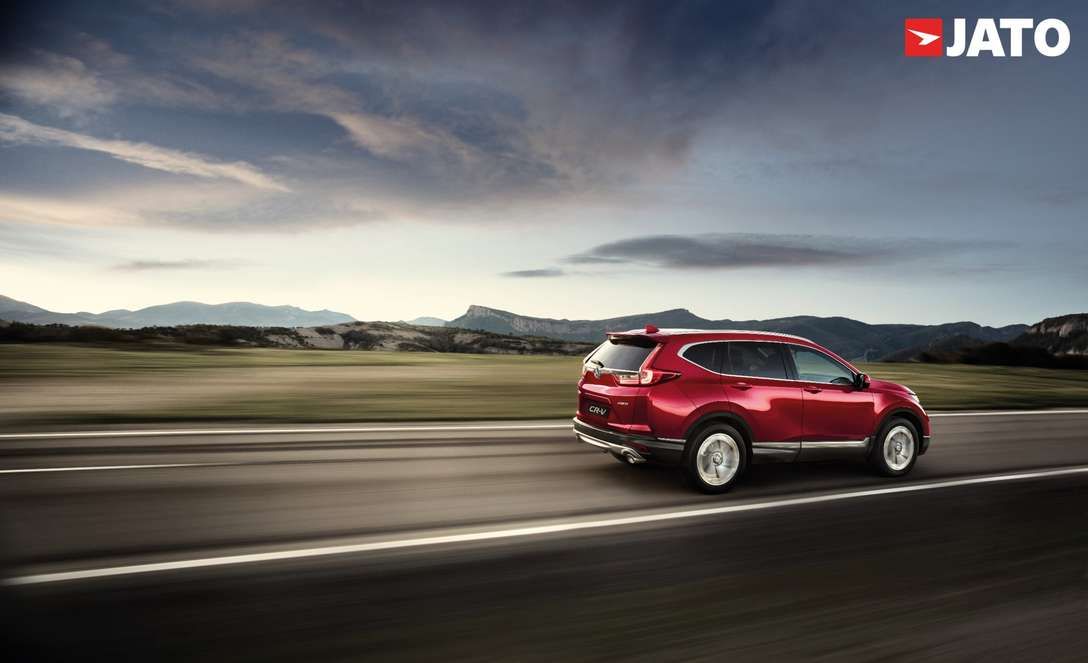 back angle of red CR-V driving up a road