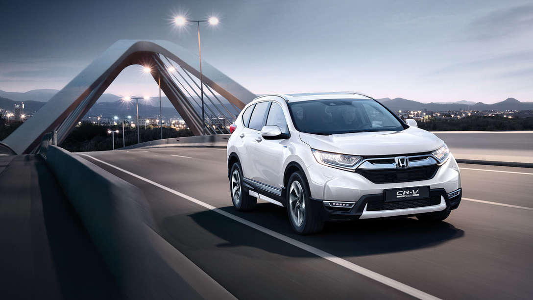 Front three-quarter facing Honda CR-V Hybrid car in street location.