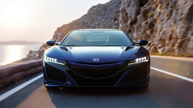 Front facing Honda NSX on a windy mountain road.