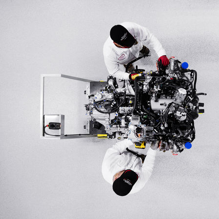 Honda NSX V6 engine with technicians.