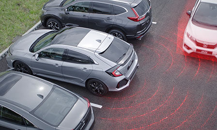 Honda Sensing car in a car park with illustration of cross traffic monitor and blind spot information.