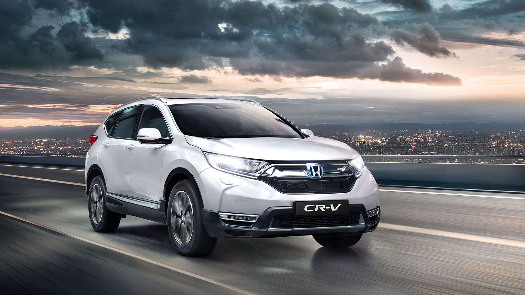 Front three-quarter facing Honda CR-V with high beam headlights on
