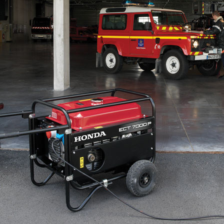 red and black honda open frame power generator in a garage with a red fire engine in the background.
