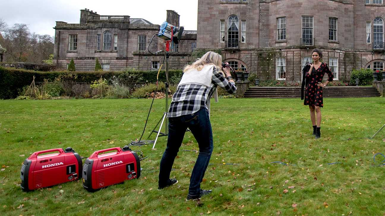 a woman using portable inverter generator to power flashgun while taking pictures.
