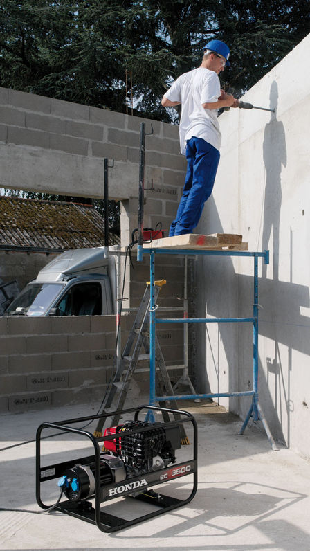 a worker on a construction site using professional power generator with strong steel frame