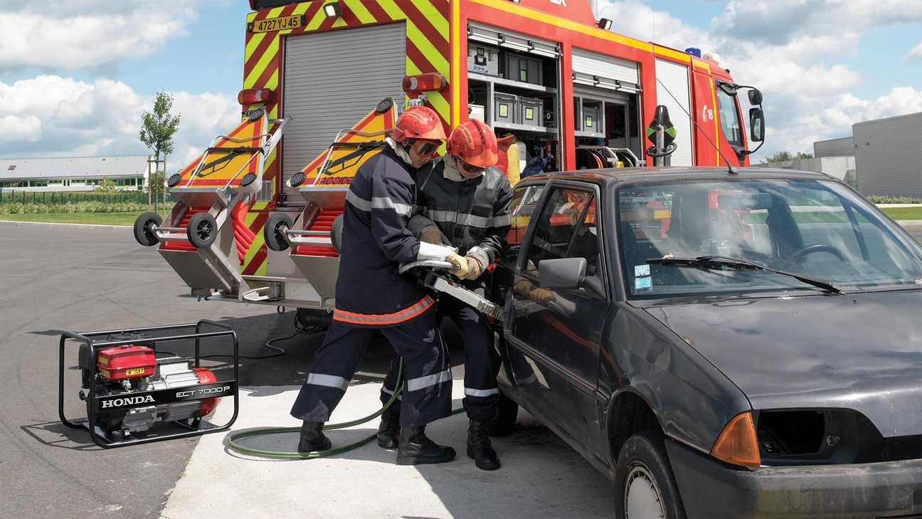 photo of two firefighters using honda open frame power generator for opening door of a black car