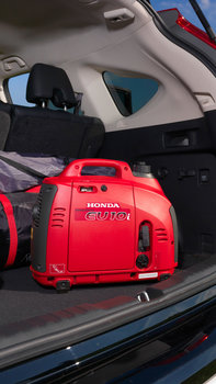 front view of honda red portable eu10 power generator in a car trunk