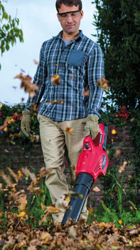 Cordless power tool blowing leaves.