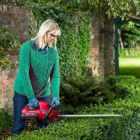 Model wearing a green jumper, trimming a hedge using cordless power tool