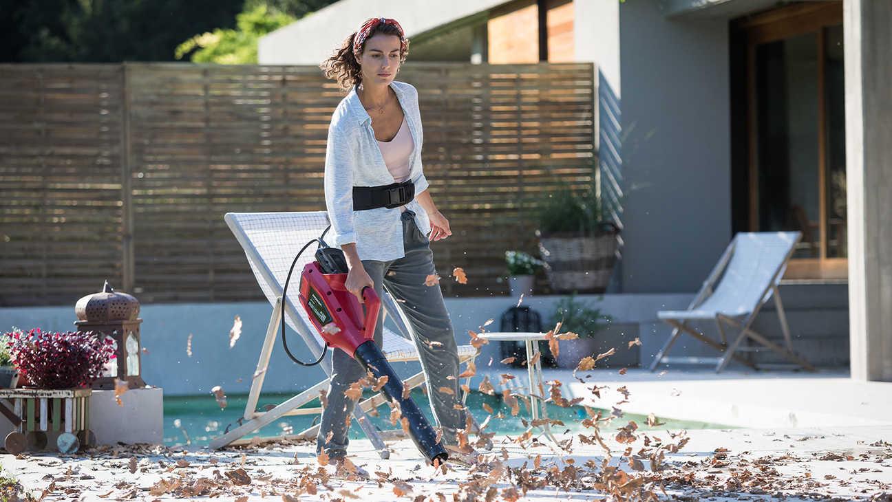 Model using Honda cordless leaf blower in garden location.