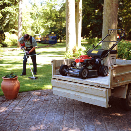 photo of honda hrh petrol lawnmower on trailer whilst man uses petrol strimmer on lawn in background