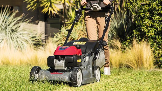 front side view of person mowing overgrown lawn with honda hrx petrol lawnmower