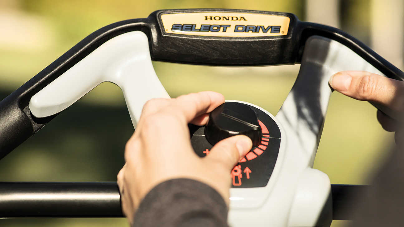 close up view of someone operating select drive controls of honda hrx petrol lawnmower