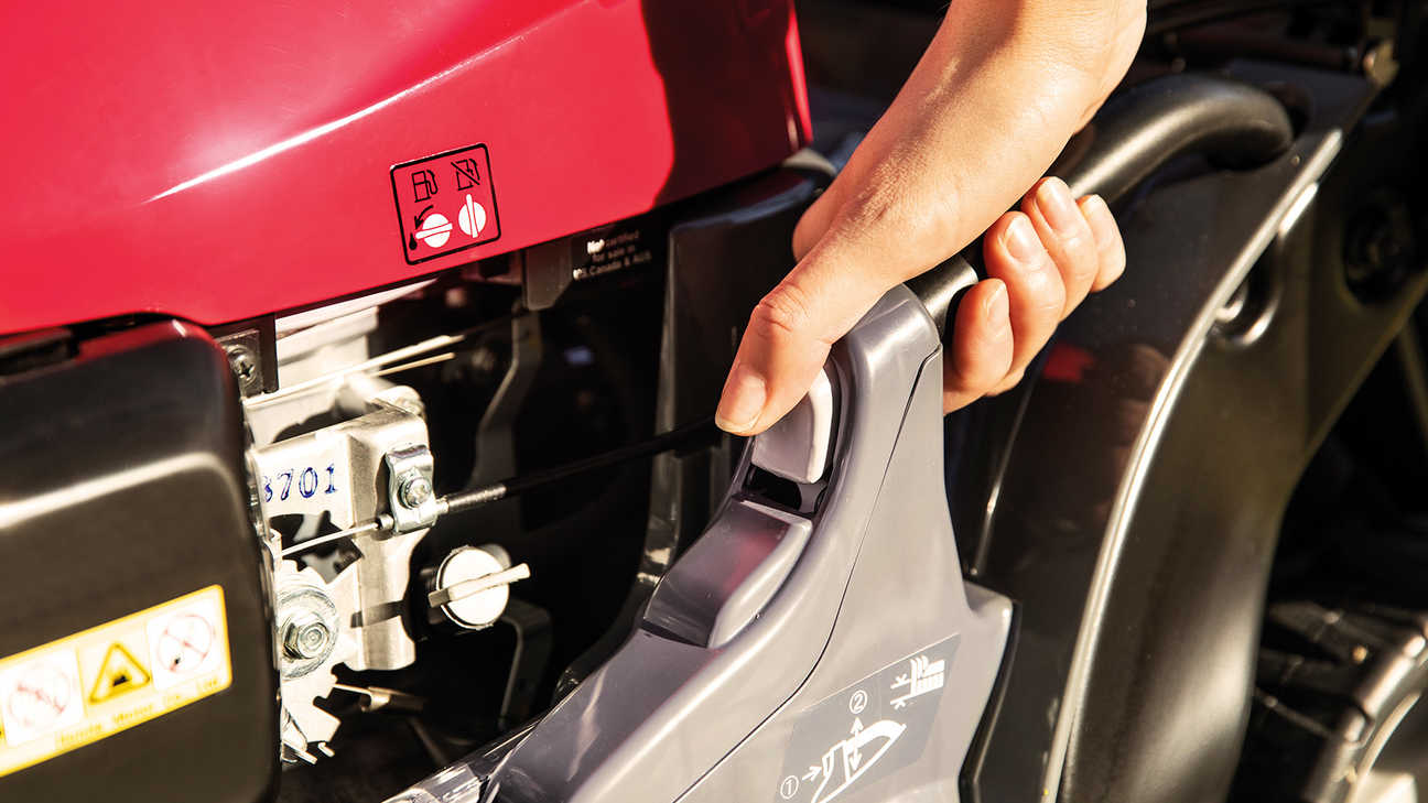 close up of person using the honda hrx petrol lawnmower with cutting height adjustment control
