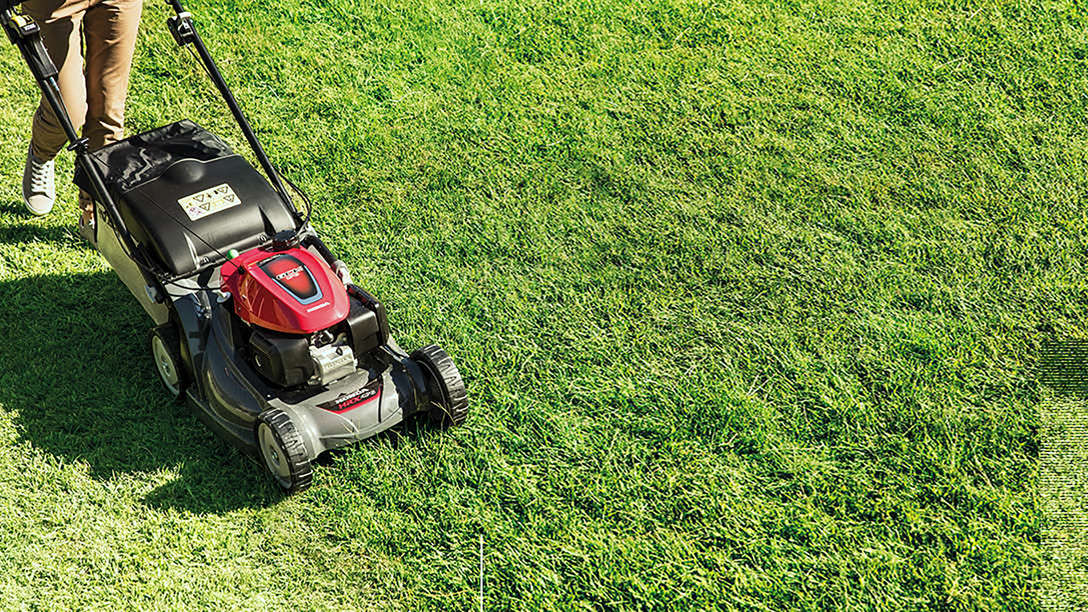 top angled view of person mowing lawn with honda hrx petrol lawnmower