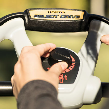 close-up of person using honda hrx petrol lawnmower select drive controls