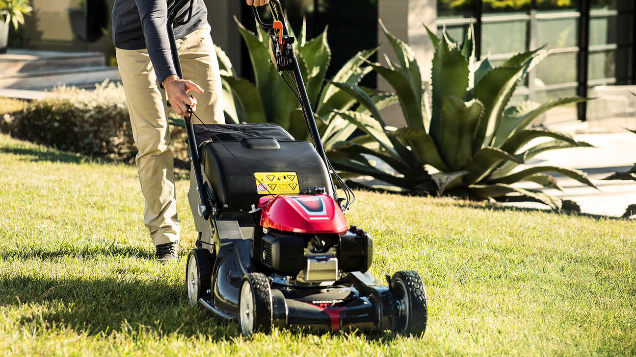 front side view of person mowing grass with honda hrx petrol mower