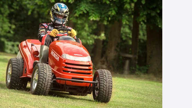 Front facing lawn tractor, being used by model, garden location.