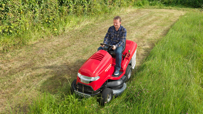 Premium lawn tractor, front three-quarter, left facing, being used by model, garden location.