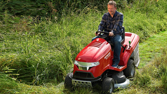 Front three-quarter, left facing premium lawn tractor, being used by model, garden location.