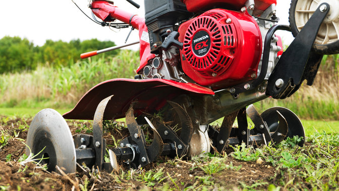 Close up of compact tiller, focusing on engine, garden location.