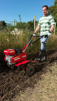 Compact tiller, being used by model, garden location.