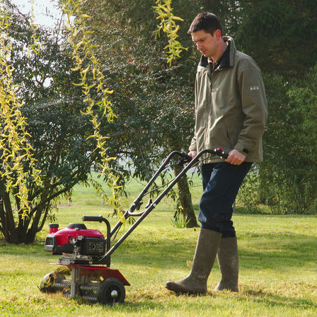Honda microtiller, de-thatching attachment, being used by model, on location.