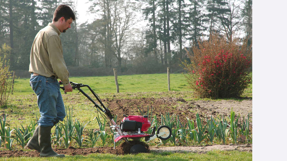 Mini tiller, right facing, being used by model, garden location.