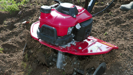 Close up of mini tiller in use, garden location.