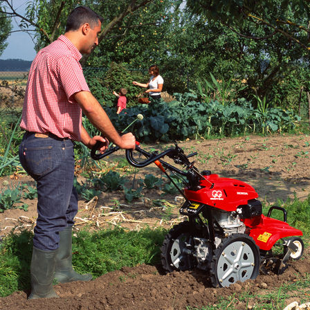 Rotary tiller, being used by model, garden location.