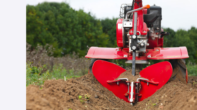 Close up of versatile tiller, garden location.