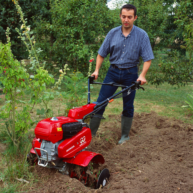 Versatile tiller, being used by model, garden location.