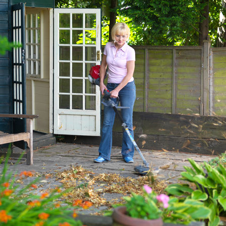 Honda Versatool with leaf blower attachment, being used by model, garden location.