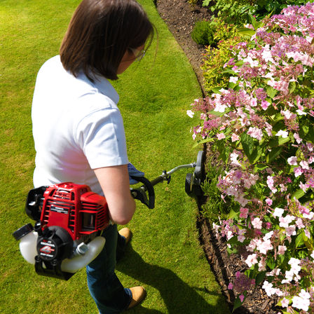 Honda Versatool, focusing on 4-stroke engine, being used by model, garden location.