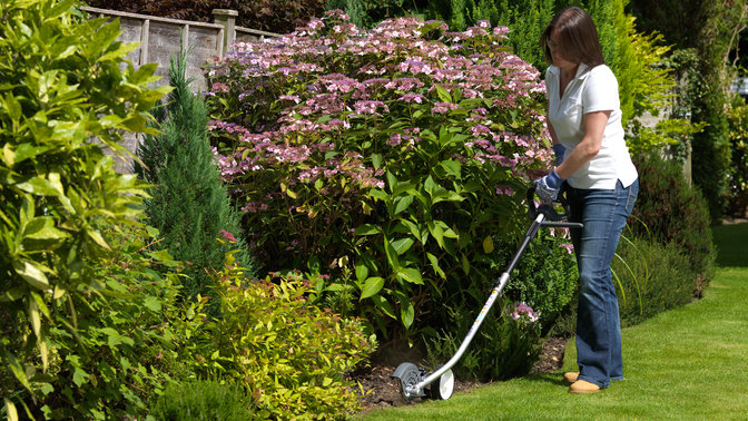 Honda Versatool with edger attachment, being used by model, garden location.