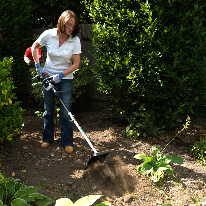 Honda Versatool with cultivator attachment, being used by model, garden location.