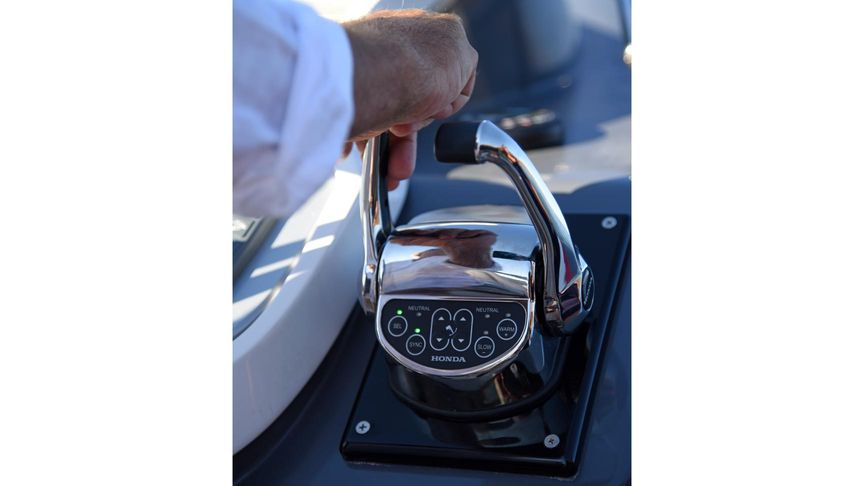 Close up of person using a Honda iST throttle control unit on a boat