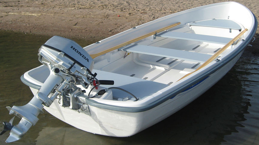 Boat on sand with Honda engine attached.