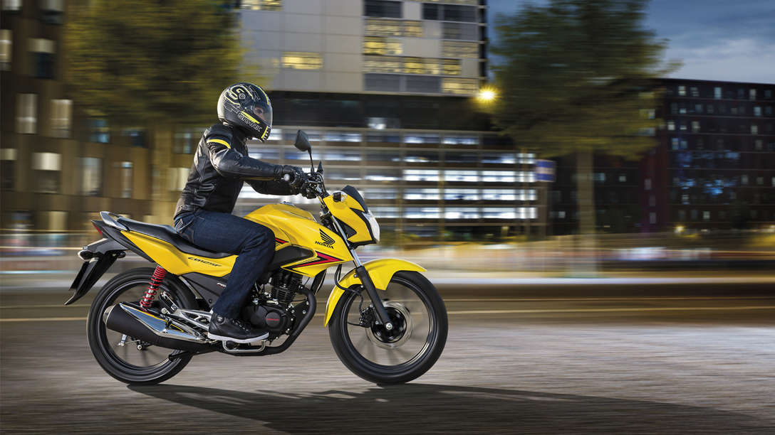 Side on, right facing CB125F in Pearl Twinkle Yellow on road (urban location)