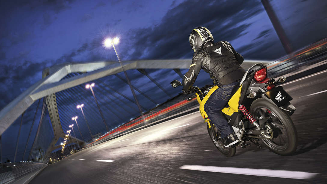 Rear three-quarter, right facing CB125F in Pearl Twinkle Yellow on road (night time urban location)
