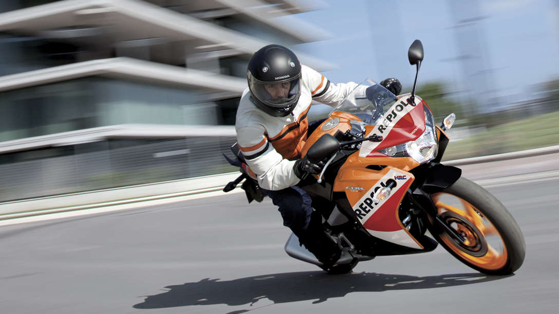 Front, 3-quarter view of CBR125 with rider leaning into turn on track location. Repsol livery.
