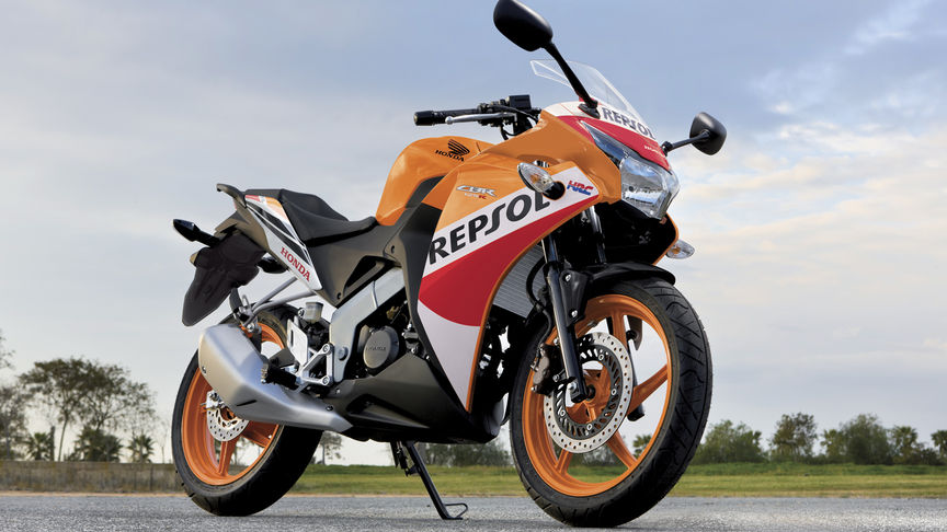 Front, 3-quarter view of CBR125, parked on track location, Repsol livery