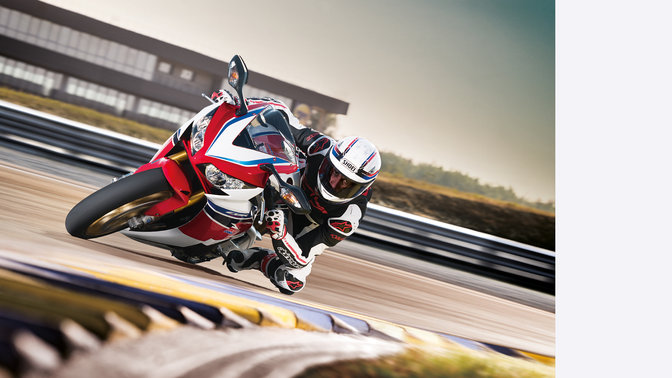 Front, 3-quarter view of Fireblade with rider, cornering in race track location. Right facing.