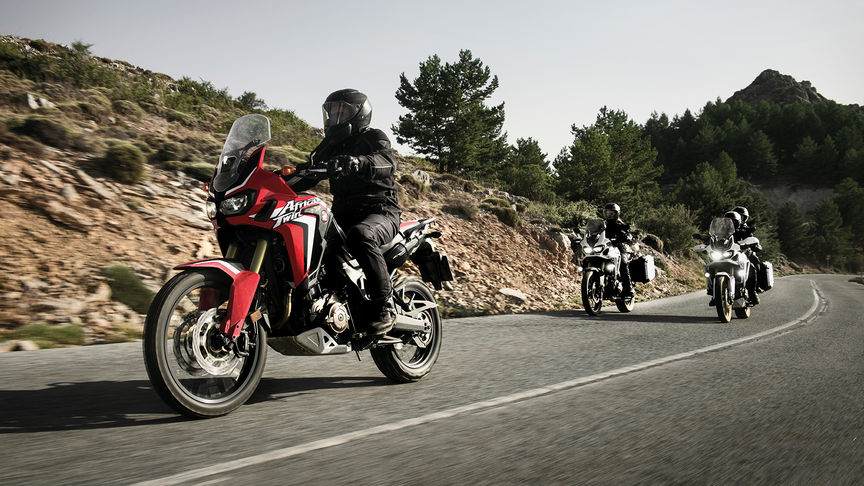 Three Africa Twin bikes coming around a bend in the road
