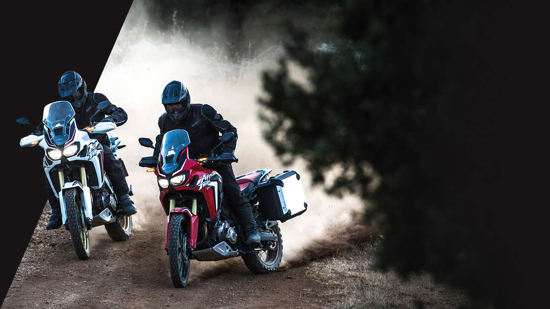 two Africa Twin motorcycles being ridden on dirt forest floor