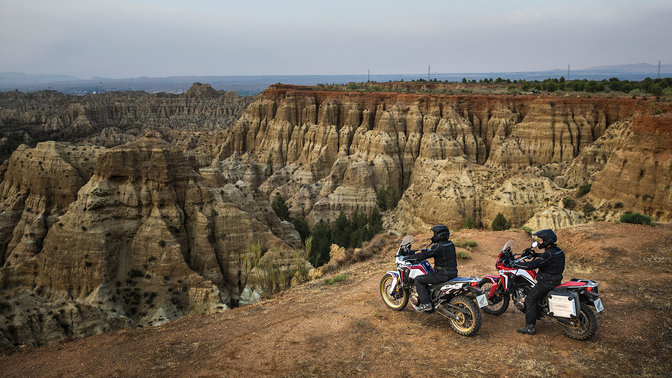 2x Honda Africa Twins with riders, looking over a canyon.